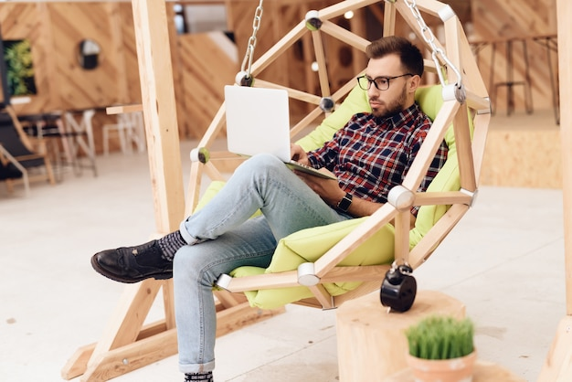 A man is sitting in a hanging chair.