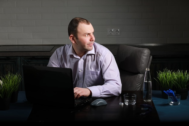 Man is sitting at his desk and working on a laptop