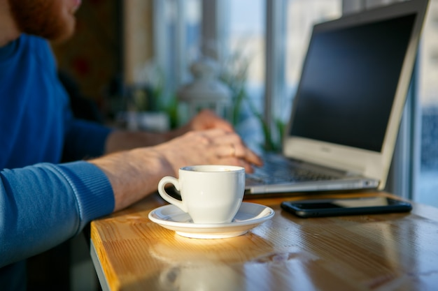 A man is sitting at a laptop next to a cup of coffee