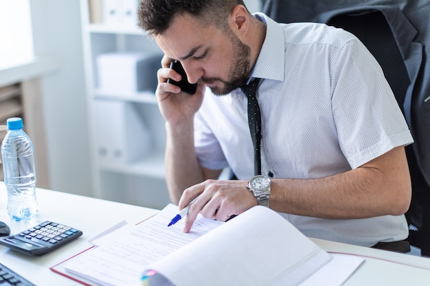 A man is sitting in the office, working with documents and talking on the phone.