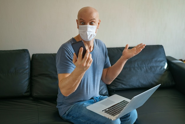 Man is sitting on a sofa in a protective mask with a laptop and phone, remote work in quarantine