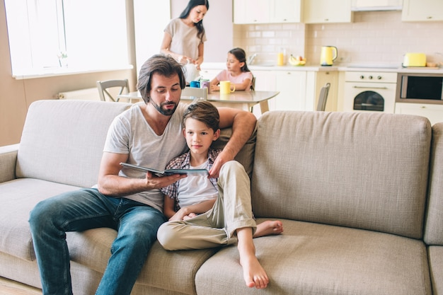 Man is sitting on sofa with his son and read a book