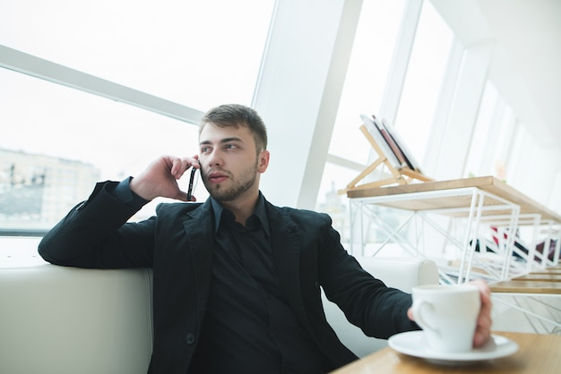 A man is sitting at a window near the window in a cafe with a modern design and speaks by telephone.