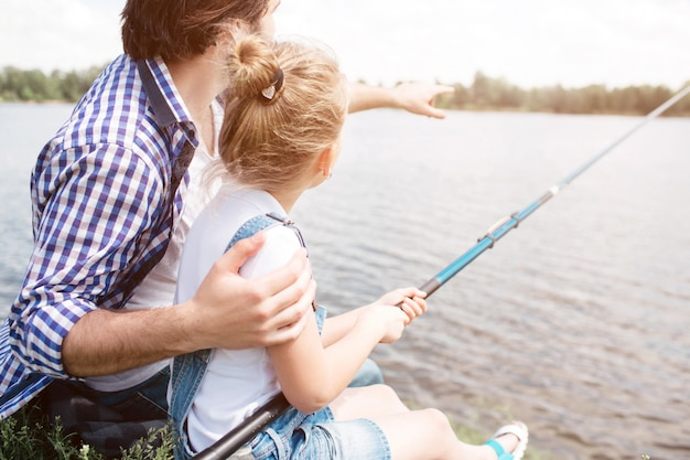 Man is sitting with his daughter at the river shore and pointing forward. girl is holding fish-rod and fishing.