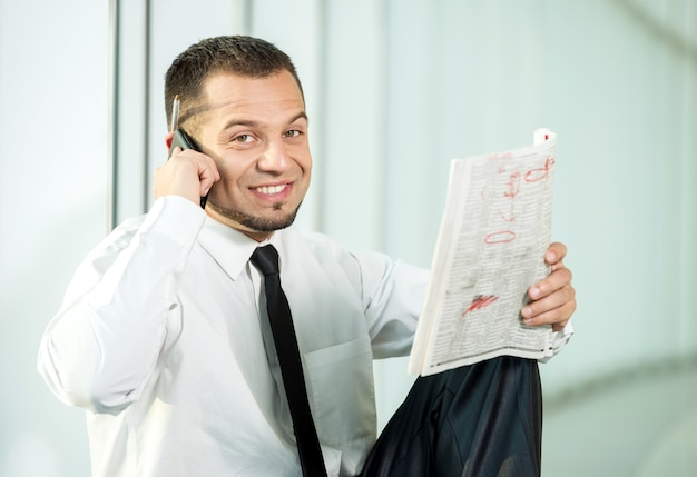 A man is sitting with a newspaper and speaking by phone.