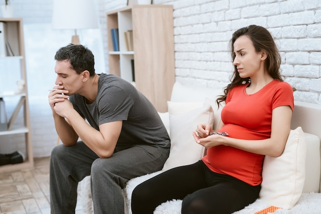 Man is smoking a cigarette next to him is his pregnant wife.