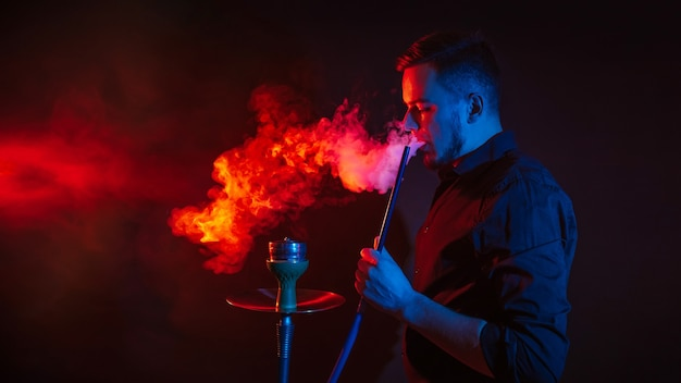 Man is smoking a hookah in a bar and blowing a cloud of smoke