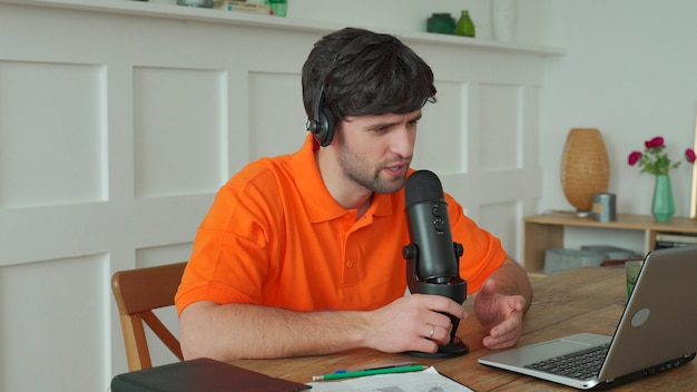 Man is speaking in microphone in studio recording podcast gesturing expressing opinions for online blog.