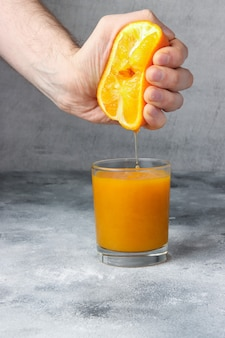 Man is squeezing orange in the glass full of fresh orange juice