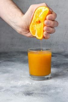 Мужчина выжимает апельсин в стакан, полный свежевыжатого апельсинового сока