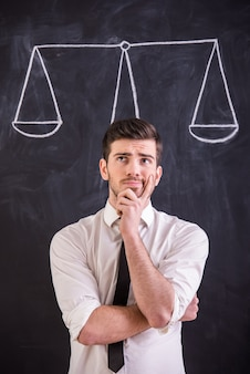 Man is standing against blackboard with drawing weight.