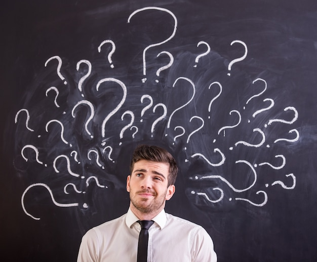 Man is standing against blackboard with question marks.