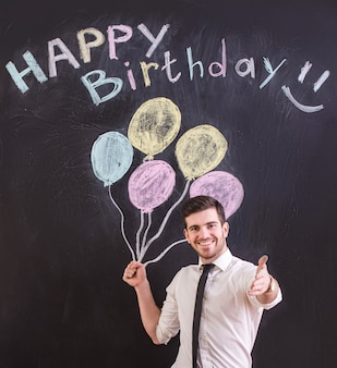 Man is standing against drawing balloon and happy birthday.