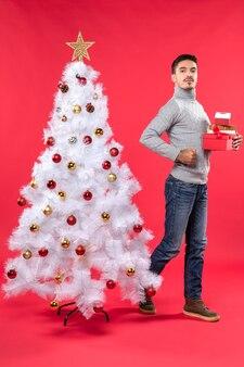 Un uomo è in piedi vicino all'albero di natale