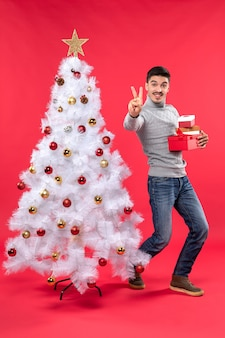 A man is standing next to the christmas tree