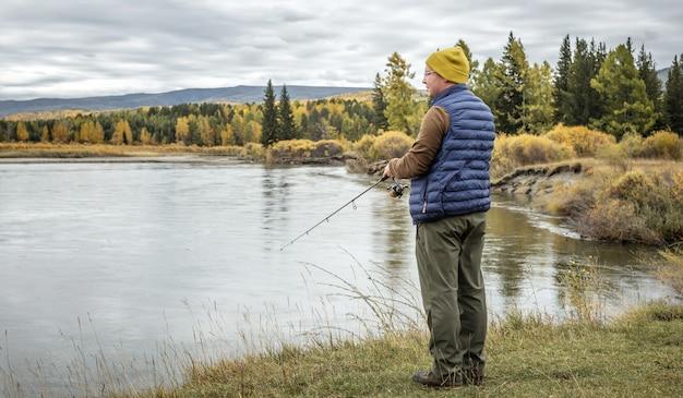男は釣り竿を手に、秋の森の川岸に立って魚を捕まえている