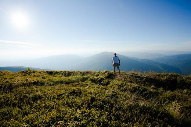 男は山の頂上に立っています。自然と旅行のインスピレーション、モチベーションとコンセプトレタリングの背景