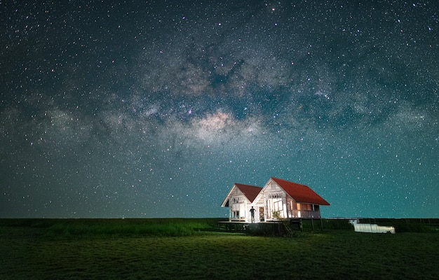 A man is standing of the twin house next to the milky way galaxy