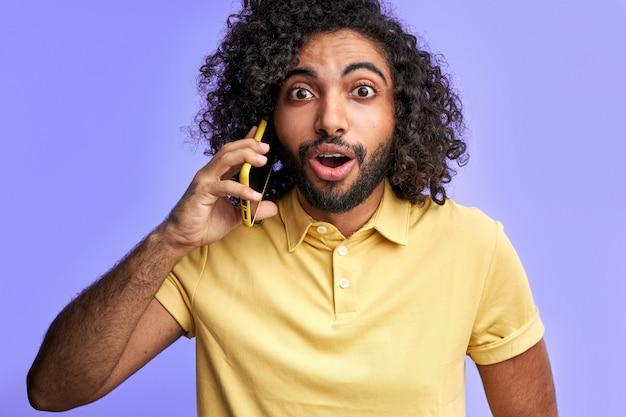 男は話に驚いて、電話で話している間友達とニュースを共有し、口を開けてカメラを見て、孤立している