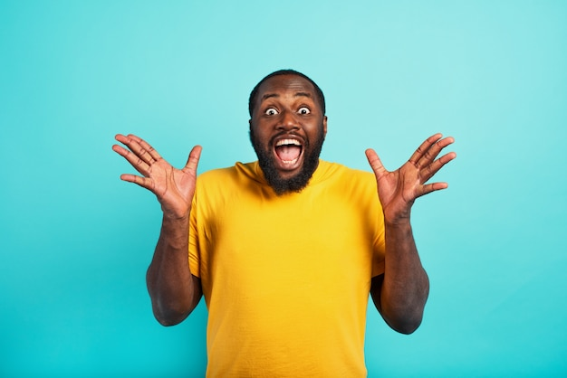 Man is surprised and excited about something. cyan wall