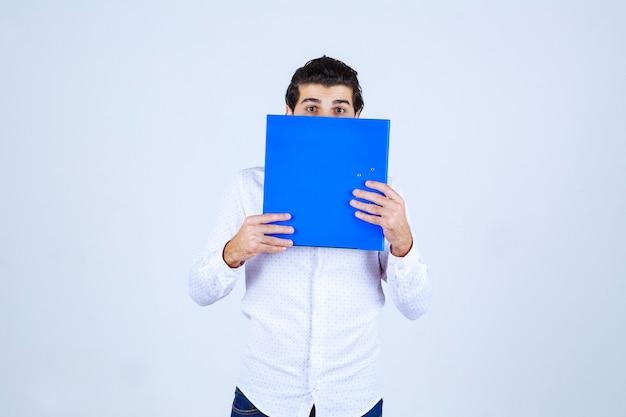 남자는 놀라서 파란색 폴더 뒤에 얼굴을 숨기고 있습니다.