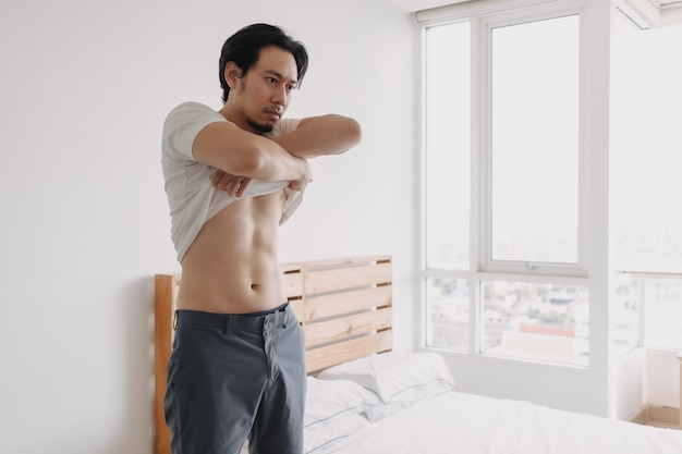 Man is taking off his tshirt in his bedroom apartment