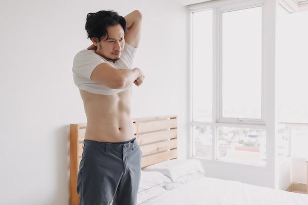 男は寝室のアパートでtシャツを脱いでいます