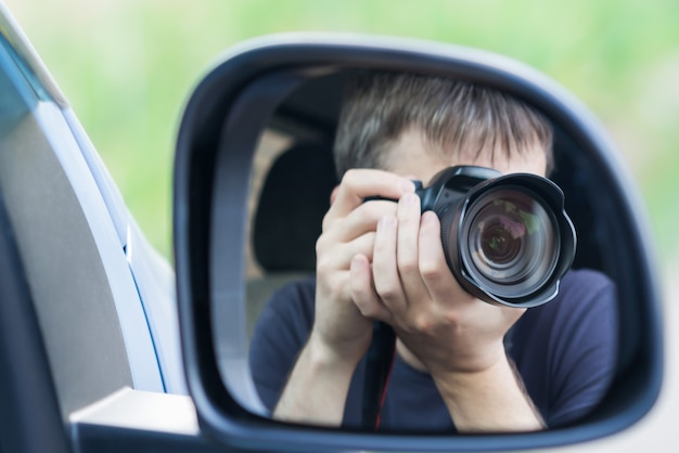 A man is taking photo someone or something from an open car window