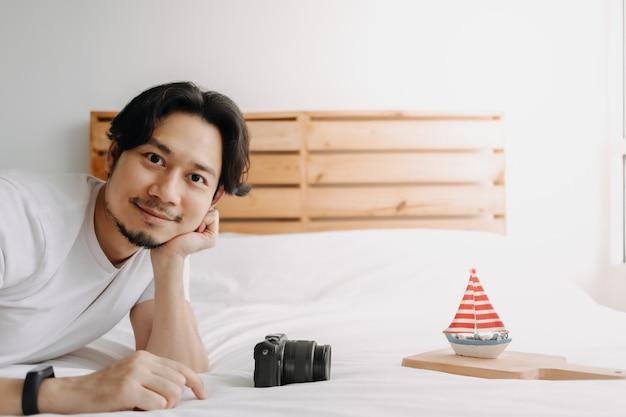 男は趣味として彼の寝室で写真のおもちゃのボートのモデルを撮っています Premium写真