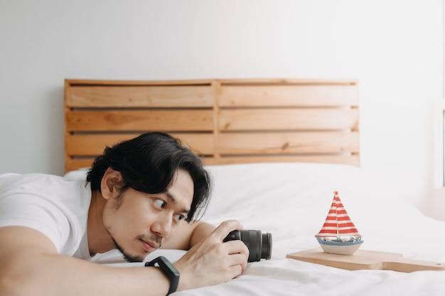 男は趣味として彼の寝室で写真のおもちゃのボートのモデルを撮っています