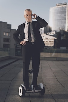 Man is talking on mobile phone on gyroboard.