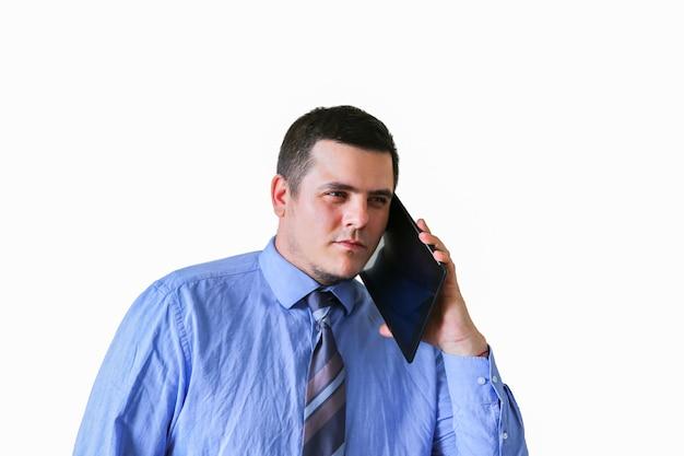 Мужчина разговаривает по планшету возле уха. изолированные на белом фоне. коммуникация новых технологий.