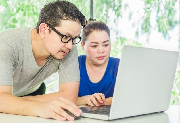 A man is training a woman working with computer in modern office