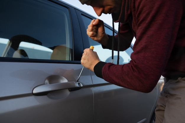 A man is trying to break the car lock in order to steal it from the parking lot.