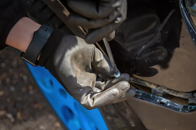 Человек пытается починить бампер автомобиля винты в отвертке для крепления руки в черной перчатке