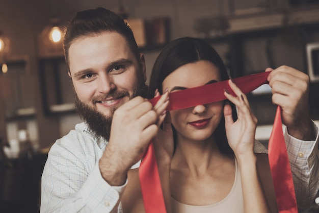 A man is tying a beautiful girl with a red ribbon