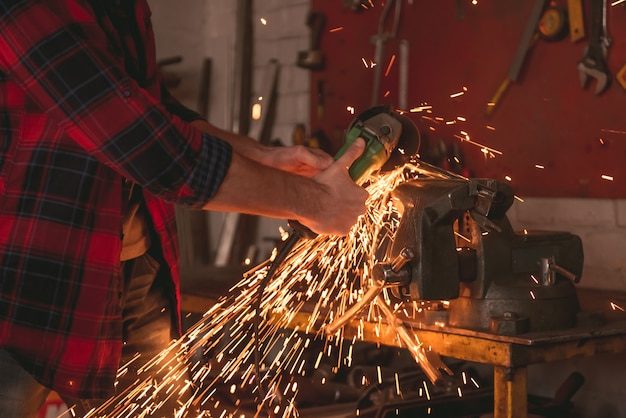 Man is using an angle grinder while working in repair shop.