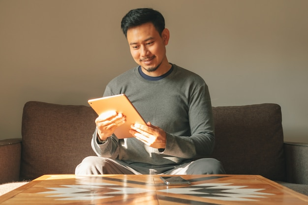 Man is using his smart tablet device in his living room apartment.