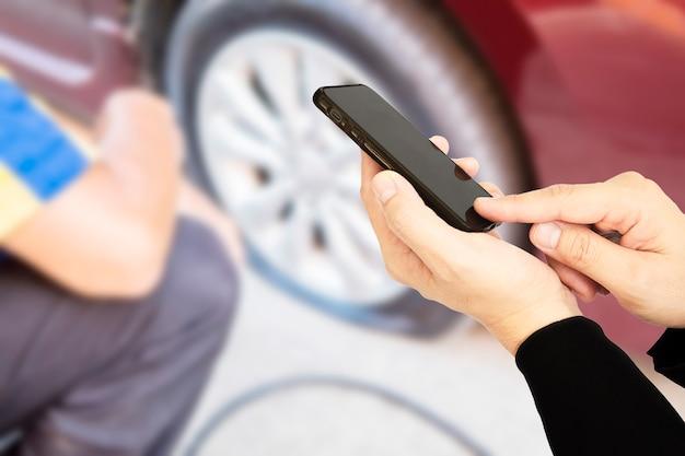 男は車のフラットタイヤの背景の上に誰かを呼び出す携帯電話を使用しています。