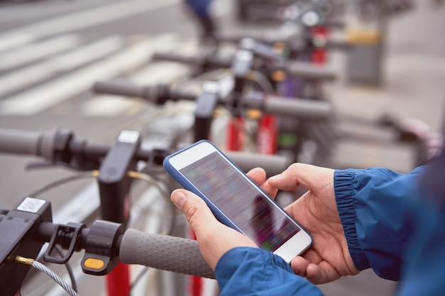 男性はスマートフォンを使用してqrコードをスキャンし、屋外で電動プッシュスクーターをレンタルしています
