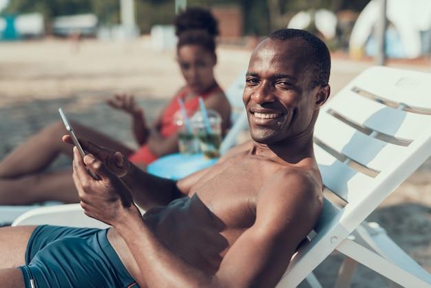 男はビーチでタブレットpcを使用しています