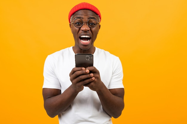 The man is very surprised looking at the screen of his smartphone