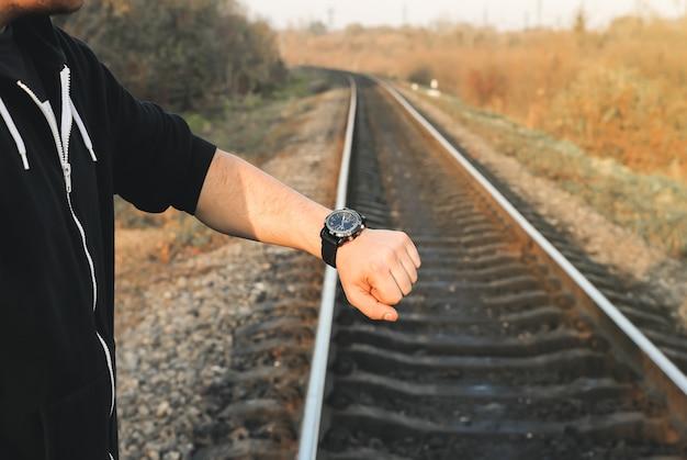 男は屋外の線路で電車を待っています。旅行のコンセプト。夏のアイデア。遅い輸送。同様の記号で親指を持ち上げます。手持ちの時計を見ている男。