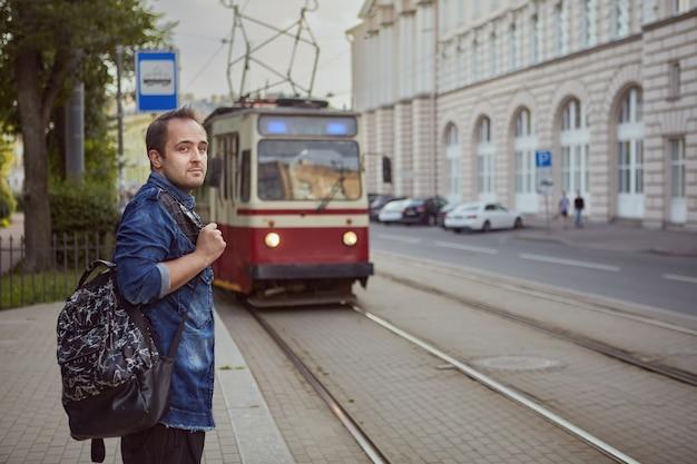 Мужчина ждет трамвай на остановке общественного транспорта.