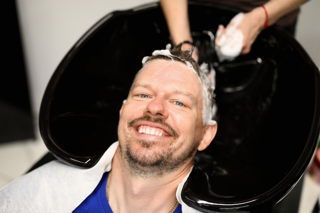 Man is washed his hair in beauty salon after haircut.