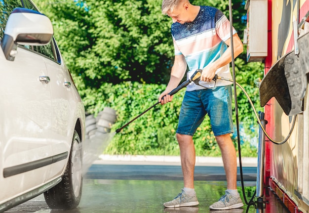 Man is washing car with high pressure water