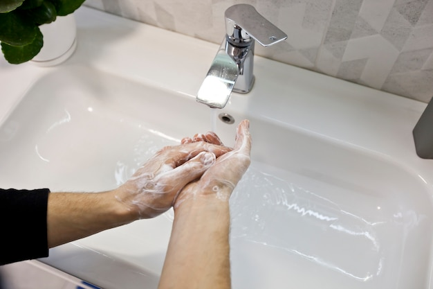 The man is washing hands with soap in the bathroom