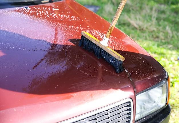 男は古い車を洗っています。屋外での車両の清掃。ウェットモップ。