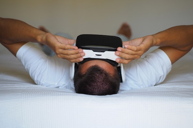 A man is watching a 3d video in a virtual reality helmet lying on the bed.