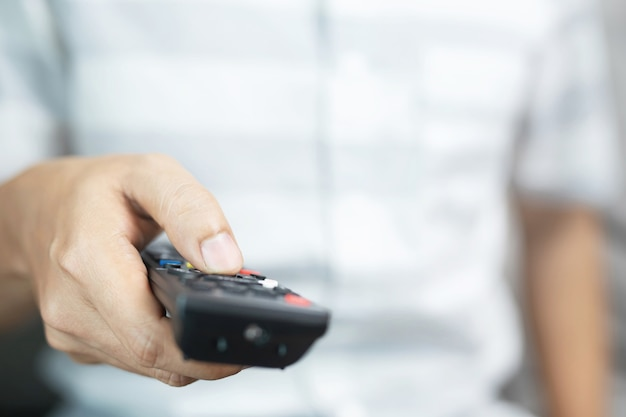 Man is watching tv with remote control in hand.